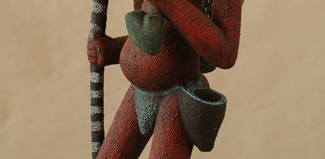 Bamileke/Kamerun -  Postać kobiety, drewno pokryte koralikami szklanymi, muszelki kauri, wys 146 cm.